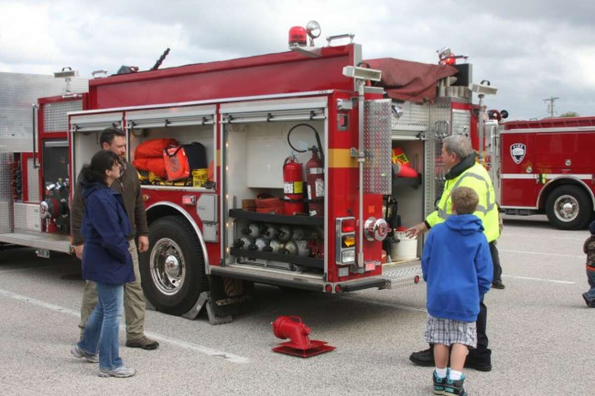 Filer Township fire chief Ron Gutowski shows a family some the gear on a fire truck at Sunday's Fire Prevention Week Festival.