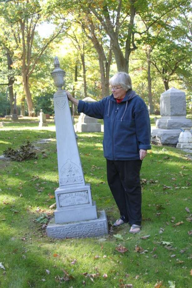 Susan Lund-Coyle shows off one of the white bronze monuments that are located at Oak Grove Cemetery. The monument is one of the many unique things that will be featured in the Cemetery Tour this year. The tour will take place at 4 p.m. on Oct. 18,19, 25 and 26.
