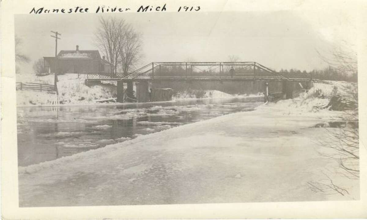 This 1913 photograph shows one of the bridges in the county over the Manistee River.