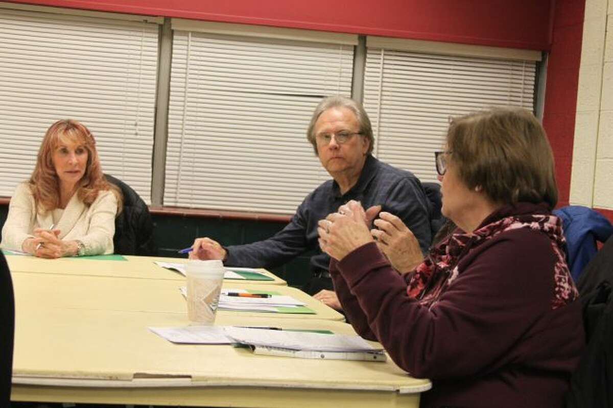 Members of the CASMAN Academy Board of Education discuss the budget amendments that were recommended by Manistee County Business Cooperative finance director Kris Mauntler.