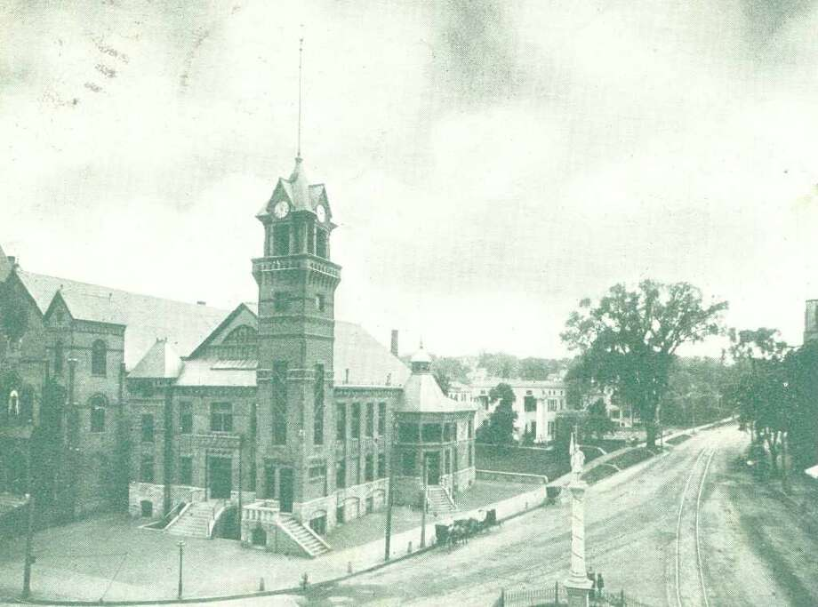 A postcard mailed in 1906 shows this image of West Street, with City Hall, the Methodist Church and trolley tracks, visible in the scene. While the cityscape has changed since then, the statue in the foreground can still be seen at the intersection of West and Main Streets in Danbury. Photo: Contributed Photo / The News-Times Contributed