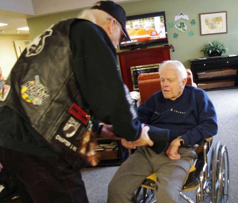 Rev. Doug Welch of Rolling Thunder Michigan Chapter One presents a sweatshirt to veteran Ed Probeck at Oakview Medical Care Facility in Ludington. (Dave Yarnell/News Advocate)