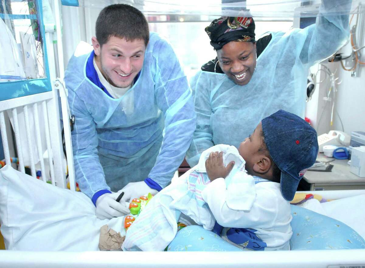 sp-hospital visit-ag-1/16/09 Dan Orlovsky (left) visits with Jaheim Taylor, 19 months, and his mother, Monica Taylor, of Hamden at the Pediatric Intensive Care Unit at Yale-New Haven Children's Hospital on 1/16/2009. Photo by Arnold Gold AG0295A