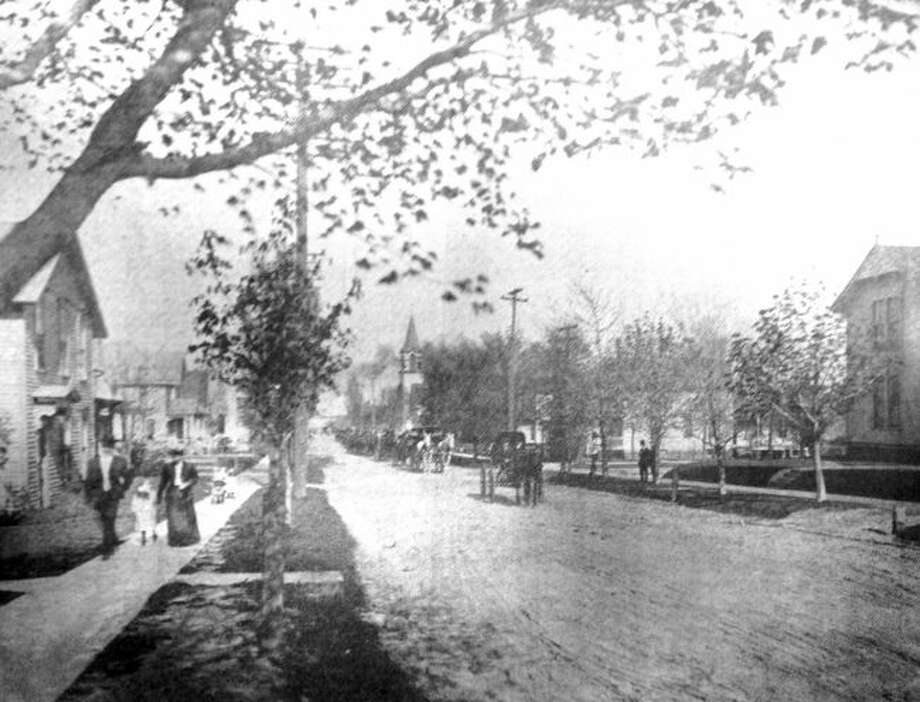 A funeral procession made up of horse and buggies makes it way on Fifth Street looking east from Sycamore Street in this 1900 photograph.