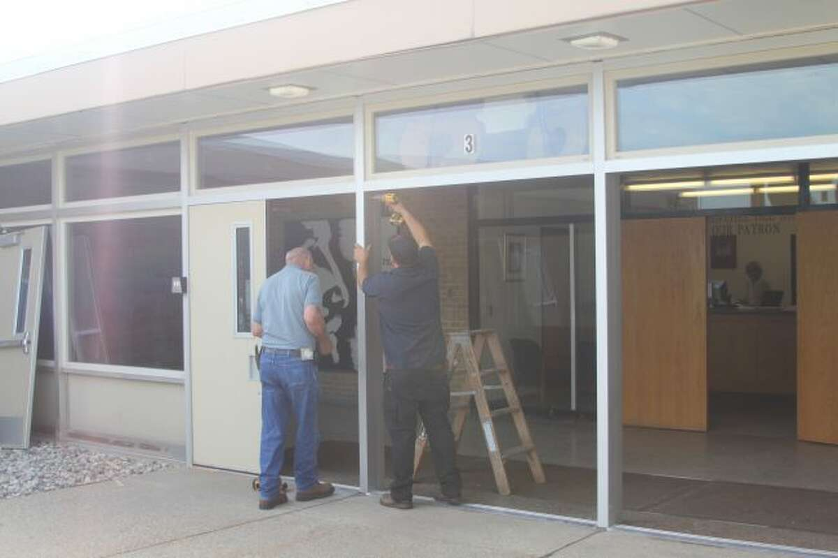 Workers from Interstate Glass replace the front doors at Manistee Catholic Central on Thursday morning. School districts throughout the county are working on completing summer improvement projects.