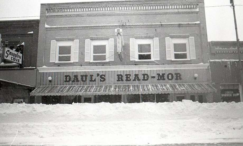 This 1978 photograph shows the high snow piles located in front of the Daul's Read Mor on River Street. That year produced a high amount of snowfall in the Manistee area.