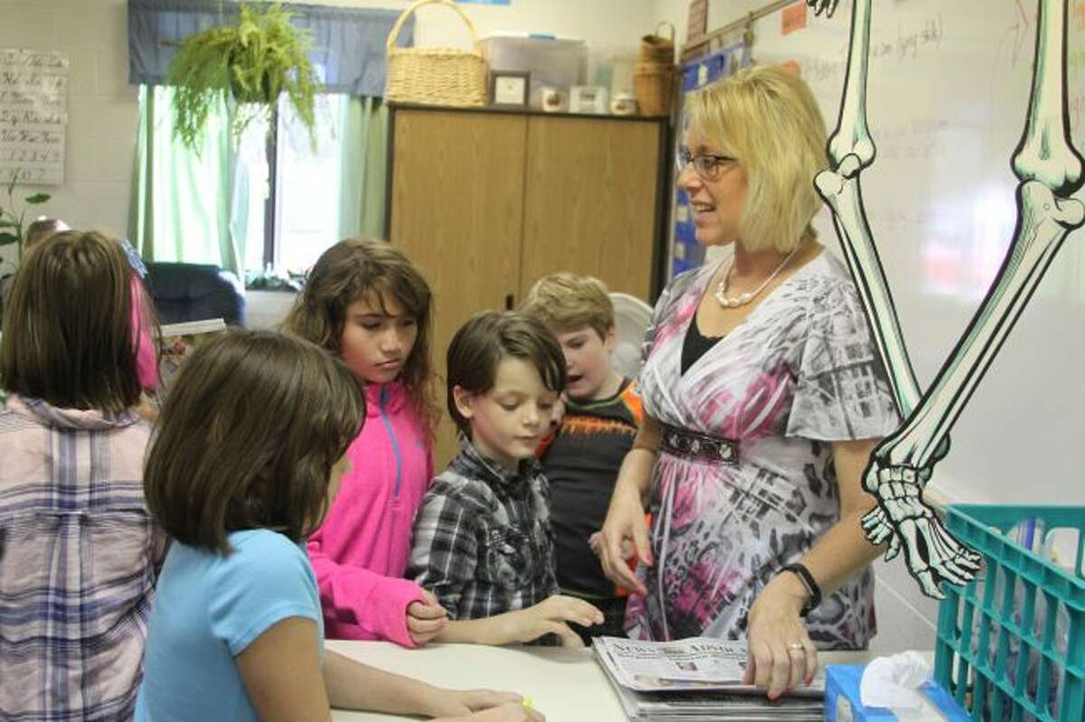 Brethren Elementary School third grade teacher McAnn Bradford passes out copies of the News Advocate for her students to use in the Newsapers in Education program.
