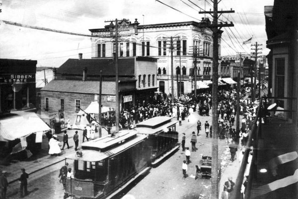 Downtown Manistee is shown in this photograph from the very early 1900's with the three-story Engelman building located in the background.