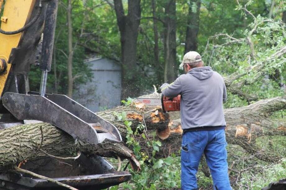 A local Habitat for Humanity volunteer slices into a large tree on a vacant property in Eastlake, which will be the site of their spring of 2020 build. (Ashlyn Korienek/News Advocate)