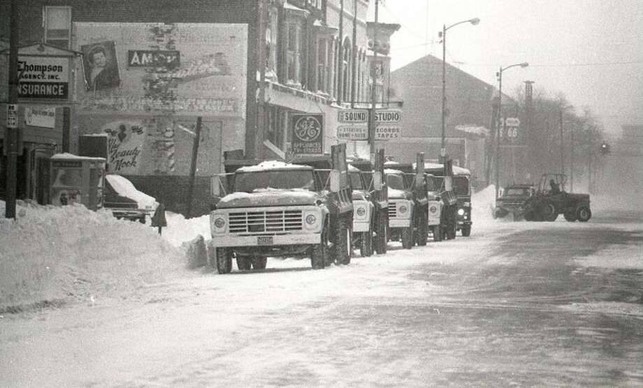 This 1970s photograph shows the east view of River Street after a winter storm as city department of public works trucks line up to collect the snow.
