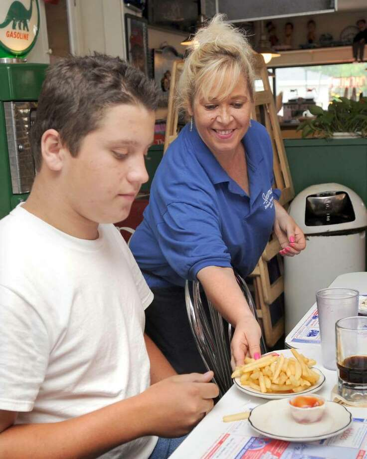 Kathy Austin, 40, of Bethel serves fries to Anthony Russo, 13, of Southbury, at the Sycamore Drive-In Restaurant in Bethel. Austin, a co-owner of Sycamore, raised $572 to give to a Korean War veteran who was robbed of donations was collecting. Photo taken Monday, August 2, 2010. Photo: Carol Kaliff / The News-Times