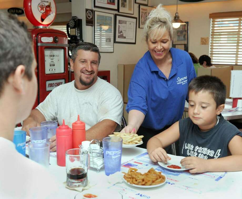 Kathy Austin serves fries to Angelo Russo and his sons Anthony, left, and Angelo at the Sycamore Drive-In Restaurant  in Bethel. The Sycamore is participating in Bethel Restaurant Week. Photo: Carol Kaliff / The News-Times