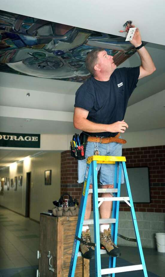 Brain Hearty of New Milford, an electrician in the maintainance department of the New Milford Public Schools, fixes emergency lighting in the front hallway of New Milford High School on Monday, August 2, 2010. Area schools are preparing for classes to start again. Photo: Carol Kaliff / The News-Times