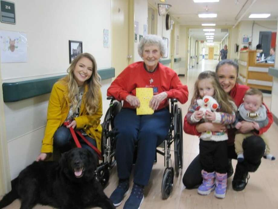 Volunteer Natalie Snyder and her therapy dog Ruger, resident Lorraine Adamski, volunteer Selena Loredo and her children, spread cheer on Feb. 14 to the residents at Manistee County Medical Care Facility. They brought homemade valentine's day cards and visited with them room to room. (Courtesy photo)