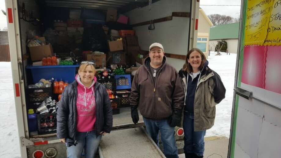 (From left) ECHO His Love director Robin Paulus, Dave Jarrett of Kaleva Meats and Shari O'Neal, ECHO Ministry Resource Center director stand in front of a truck full of items donated by Jarrett from his store after it closed. (Courtesy photo)