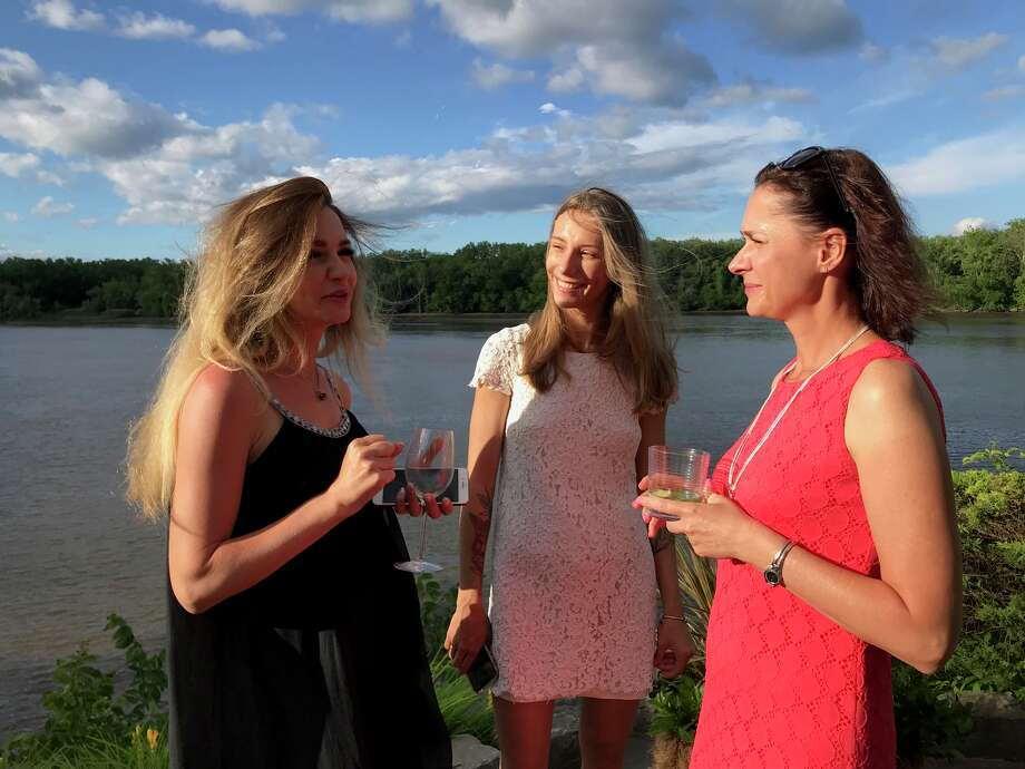Visitors from Tula, including Olesya Gulevskaya, left, Elina Kreminskaia, center, and Marina Kuperman, talk about Albany's Russian sister city at a party for the Albany-Tula Alliance recently at the Glenmont home of Charles and Charlotte Buchanan. Photo: Paul Grondahl / Times Union