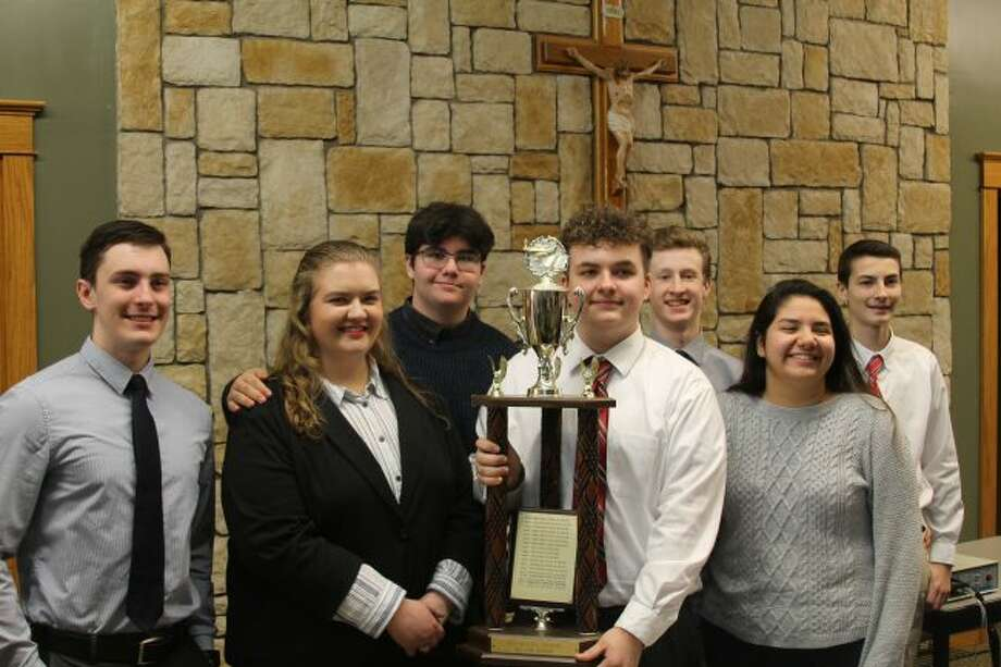 MCC Sabers Quiz Bowl team members Max Papenfuss, Joseph Buswinka, Sam Madsen, Claire Wittlieff, Blake Johnson, Henry Hybza and Elena Pizana celebrate a win for the West Michigan D League title. Sean Dougherty is not pictured. (Ashlyn Korienek/News Advocate)