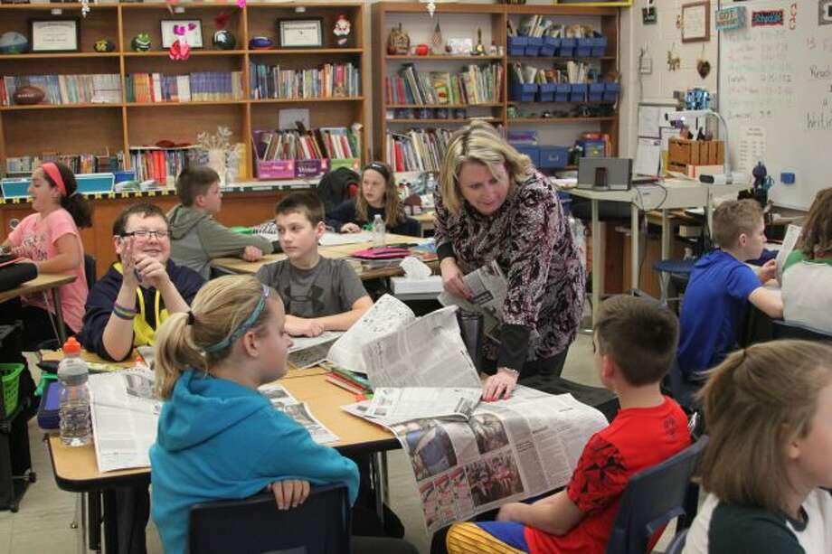 Kennedy Elementary School teacher Connie Josvai answers questions for her students as they work on assignments from stories they read in the Manistee News Advocate. Josvai has been taking part in the Newspapers in Education program for many years.
