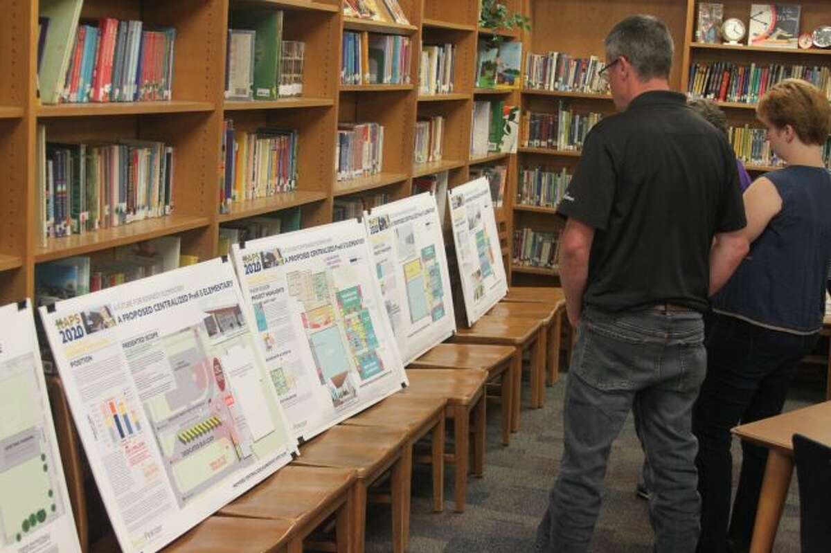 Members of the public review drawings of improvements to the MAPS buildings that would be made with a bond request at Wednesday's forum. A second forum will be held at 7 p.m. on Sept. 9 at Kennedy Elementary School for those who were unable to attend the first one.