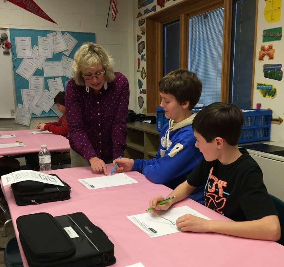 Onekama Middle School math teacher Michele Warman works with Benjamin Falk and John Burtch on the new math curriculum.