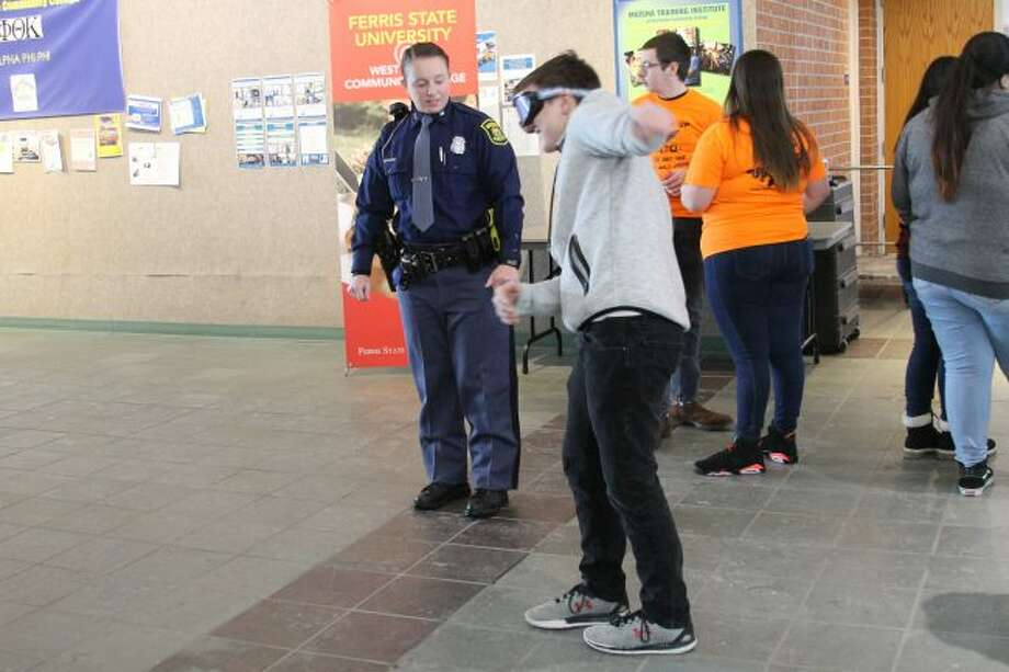 """A teen takes on a mock sobriety test wearing """"impaired driving"""" simulation goggles. (Ashlyn Korienek/News Advocate)"""