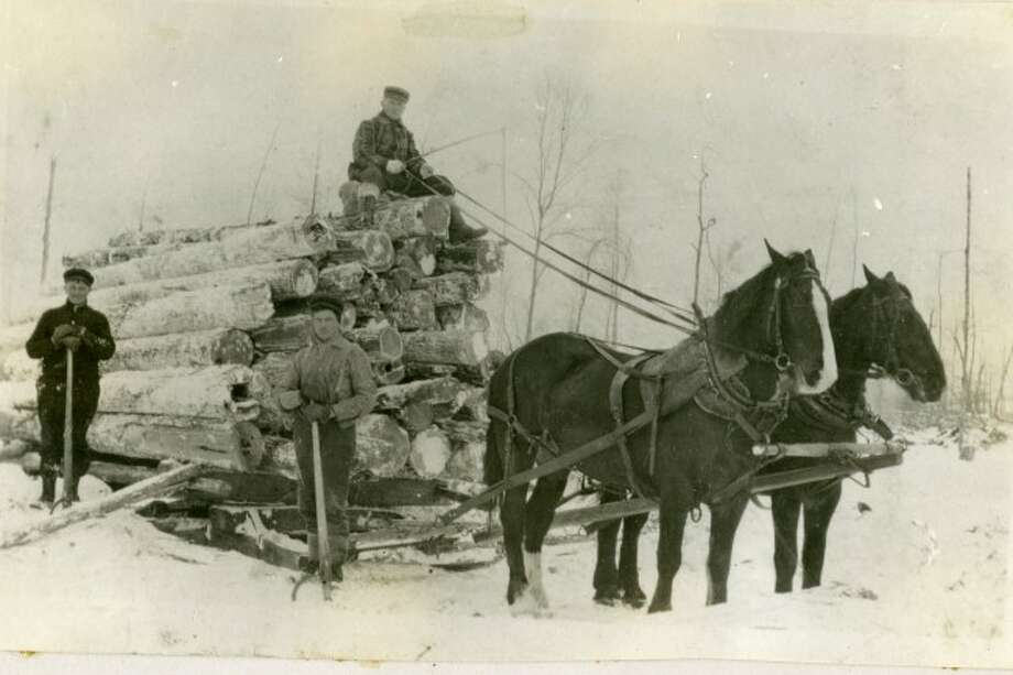 Logging camp workers kept busy throughout the winter months in the 1890s loading logs to ship to the sawmill.