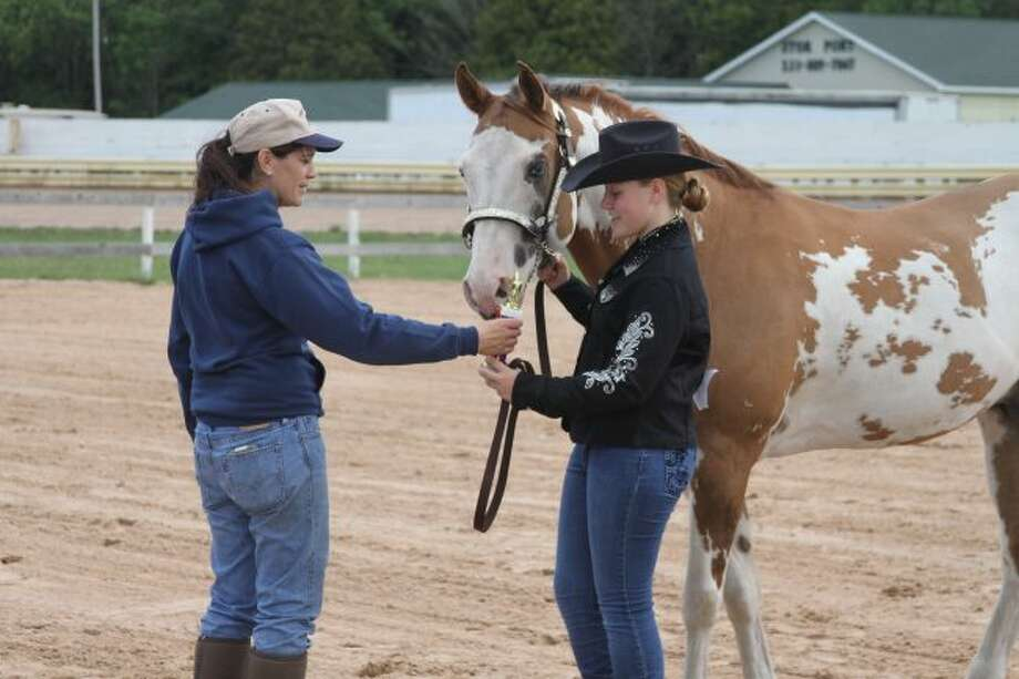 Manistee County Fair Youth/Open Horse Show co-chair Elaine Bossingham presents Tristyn Klockzien with her trophy during Sunday's competition.