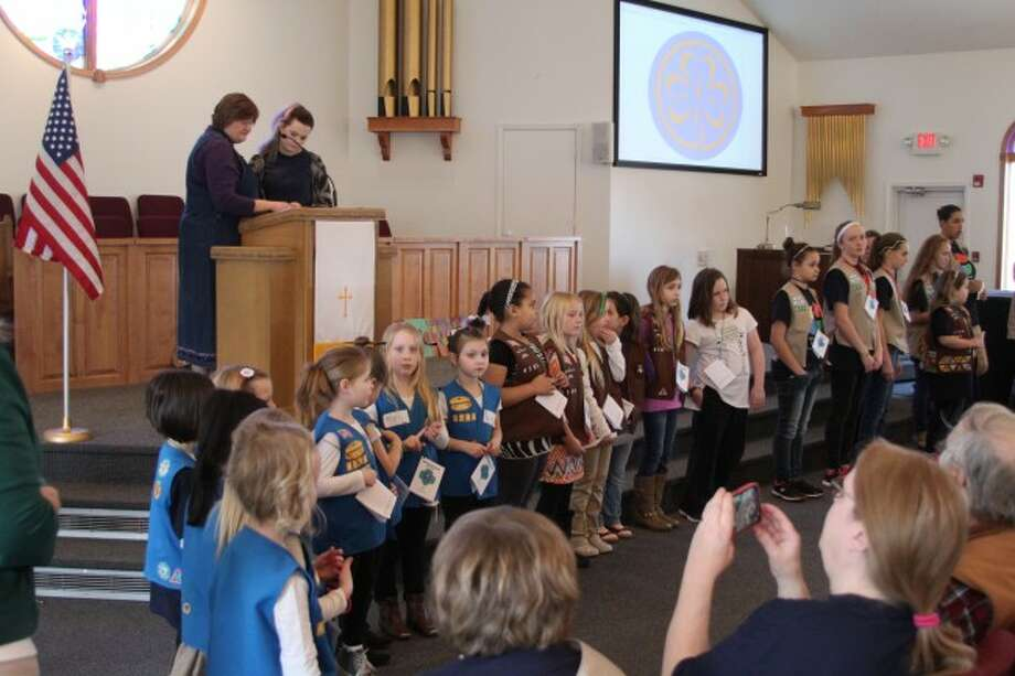 Girl Scouts of all ages gather at the front of Faith Covenant Church on Sunday for the opening ceremony on World Thinking Day.