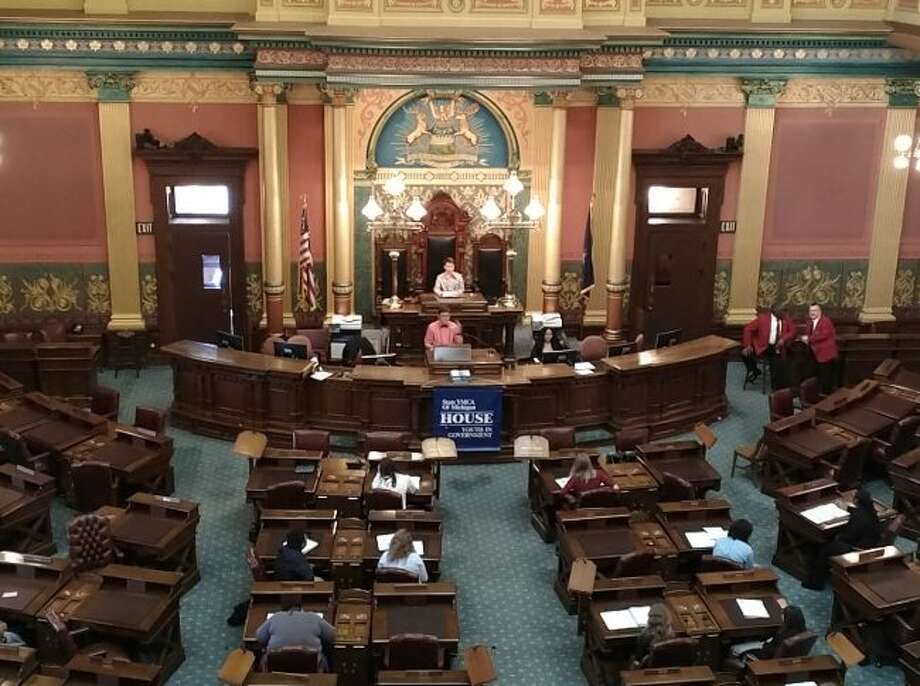 Manistee Youth in Government Ryan Biller stands at the podium of the Blue House of Representatives and reads a bill that is up for consideration. Biller served as the reading clerk at the recent conference. Manistee High School sent four students to the conference this year.
