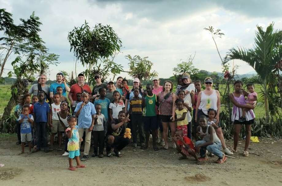 The Rotary International group from Manistee pose with the children of Villa Altagracia where they worked on one of their projects.