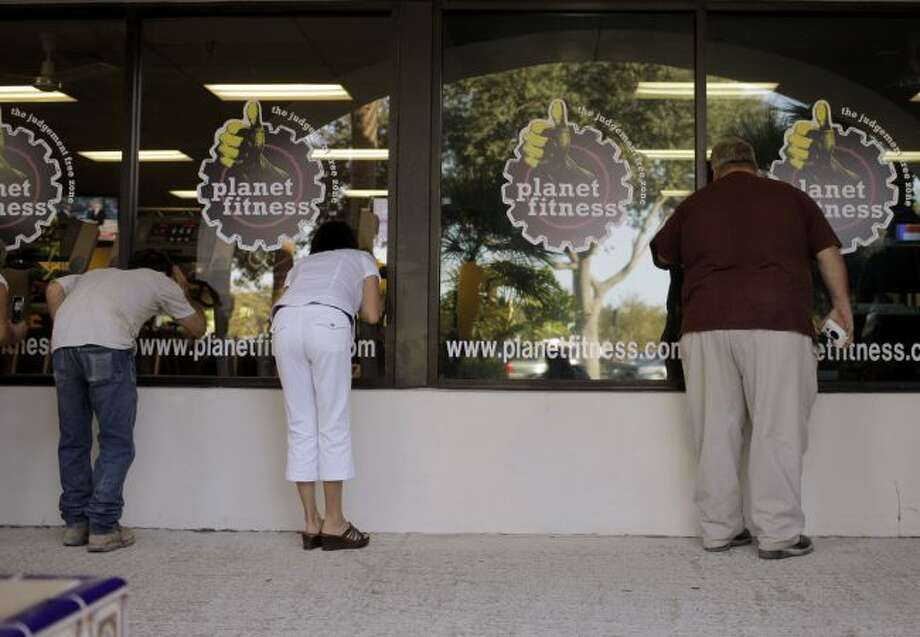 Spectators watch through the window on Oct. 21, 2008, as Democratic presidential candidate, Sen. Barack Obama, D-Ill., works out at Planet Fitness in Palm Beach, Fla. Kohl's, which is on a mission to shrink its biggest department stores, says it will lease or sell the newly empty space to Planet Fitness at 10 locations to start, but may increase that number in the future. (AP Photo/Jae C. Hong, File)