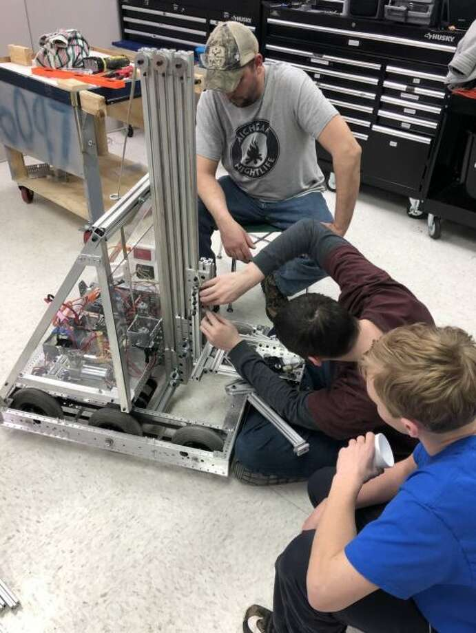 Brethren Robotics coach Tracy Hofacker watches as team members Eric Grismore and Markus Jacobs make adjustments to the team robot.
