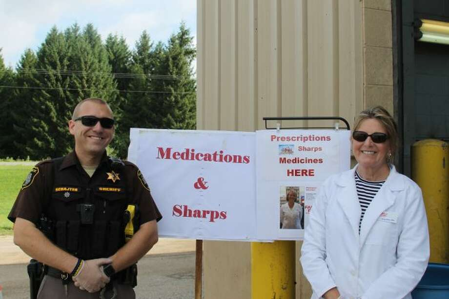 Deputy Sheriff Alex Schajter and Pharmacist Jenny Olsen accept expired prescription medicines and syringes for safe disposal at the Manistee County Road Commission garage. (Scott Fraley/News Advocate)