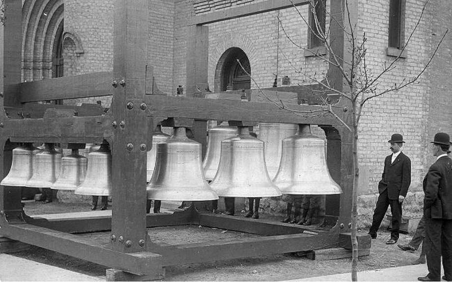 Local residents are shown in this photograph from the 1890s gathering around the bells at Guardian Angels Church in Manistee prior to the bells being installed.