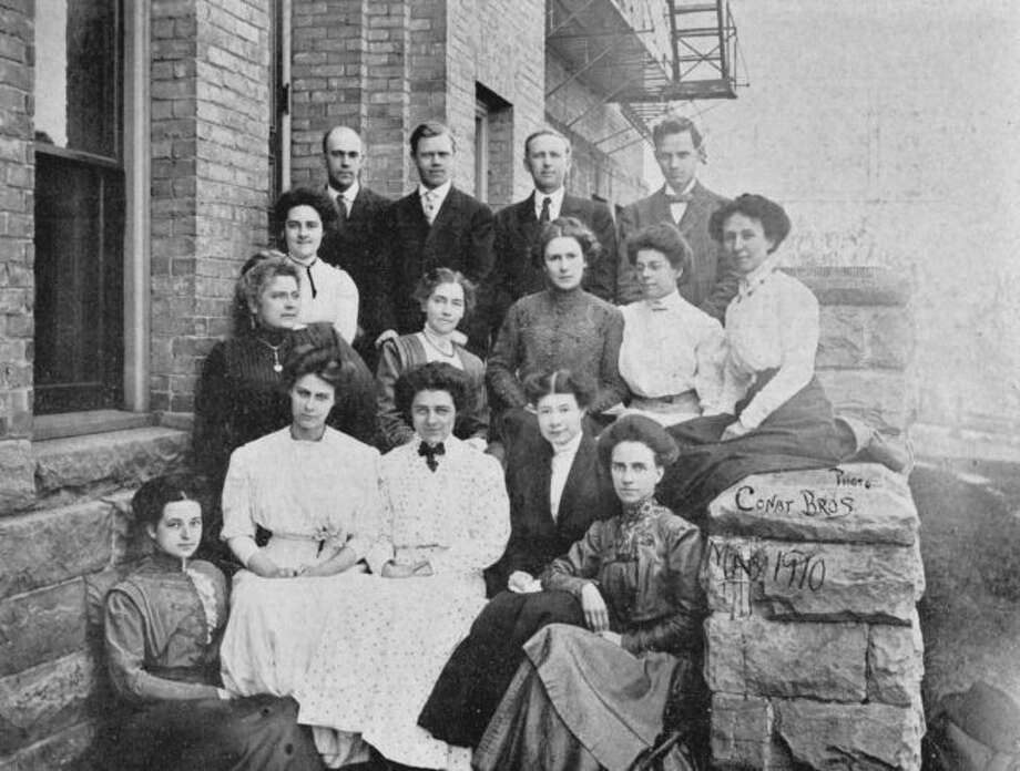 The 1910 photograph shows the faculty members of the high school in Manistee.