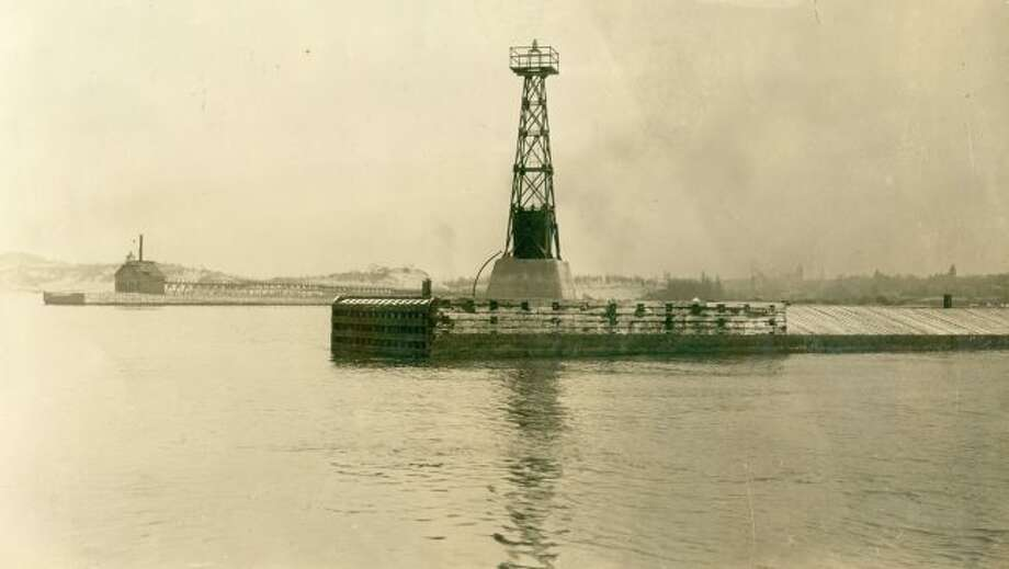 Shown is the the two break walls and lighthouses located at the Manistee Harbor entrance in the early 1900s.