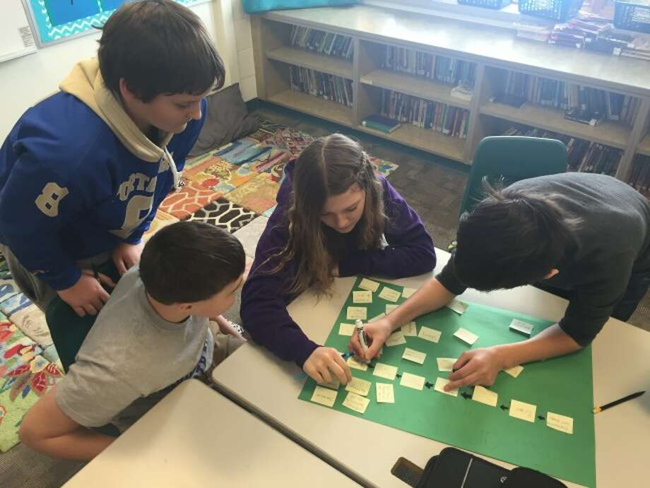 Onekama seventh grade students Jake Petrosky, Ben Falk, Ajah Fink, and Adam Porter work in cooperative groups to draw conclusions about the fall of the Roman Empire.