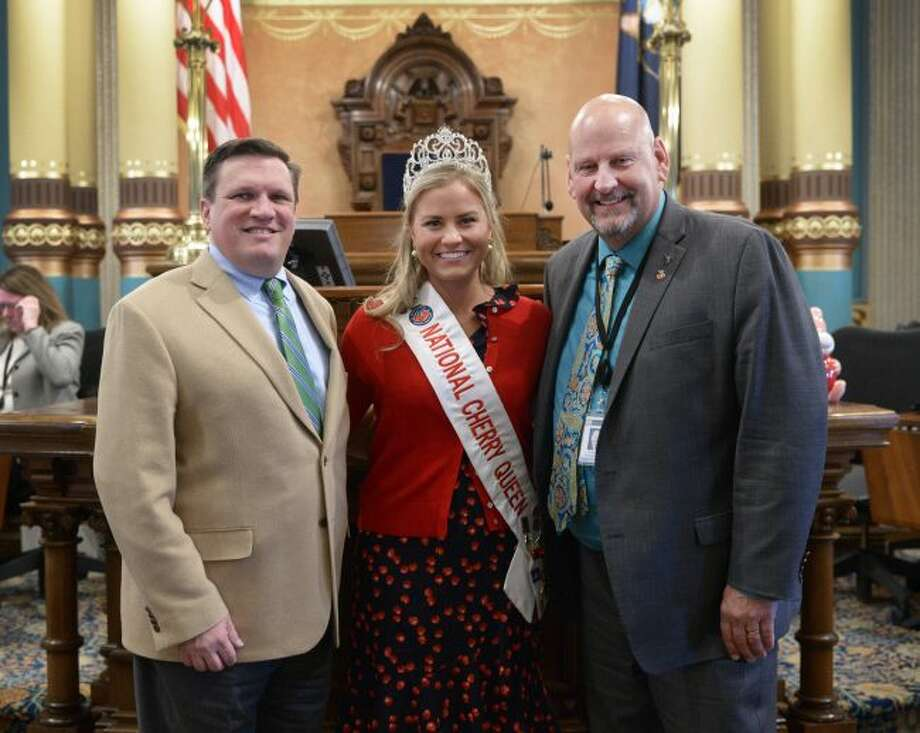 Sens. Wayne Schmidt (left), R-Traverse City, and Curt VanderWall, R-Ludington, welcomed Grace Boyles to the state Capitol on Wednesday. Boyles, who was named Michigan cherry queen last year, made the trip to Lansing for Michigan Agriculture Day at the Capitol. (Courtesy photo)