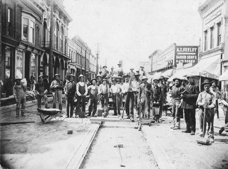 Workers of the Central Bitulithic Company, along with city workers, pose for a picture while digging up River Street west in preparation for paving in July, 1906.