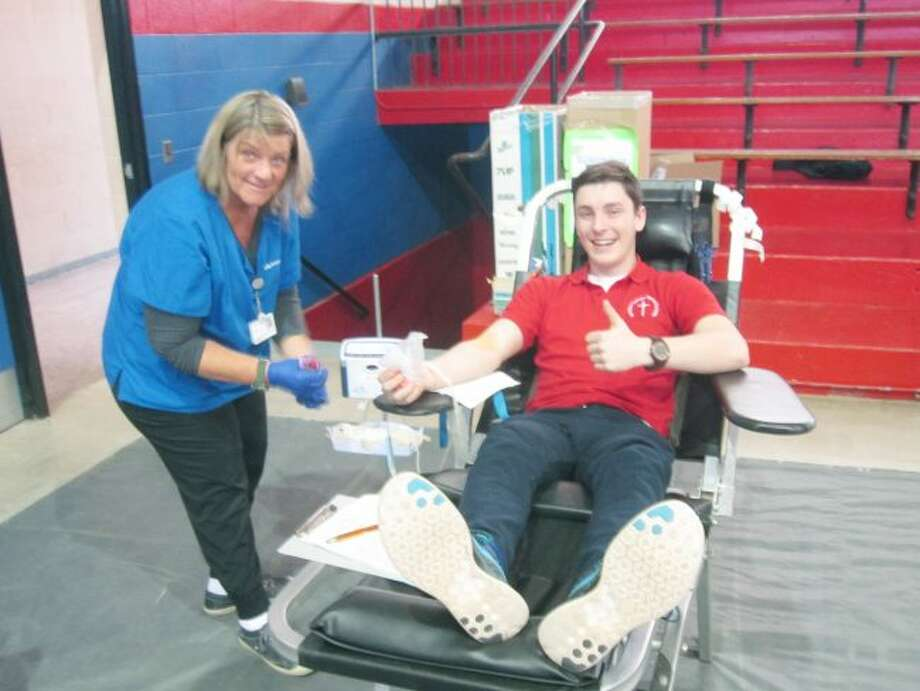 "Sophomore Joseph Buswinka gives the ""thumbs up"" as he donates his first unit of blood."