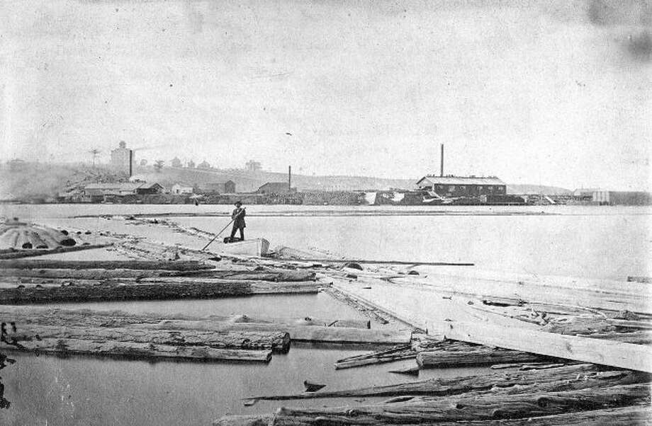 A lone lumberjack moves logs around Manistee Lake in this 1890s photograph as they prepare them for the sawmill.