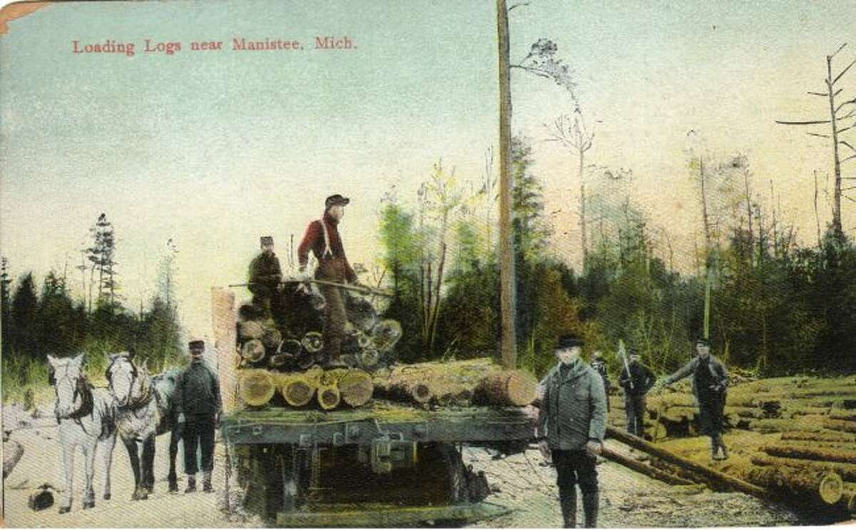 Lumberjacks load logs on a train as they prepare to ship them off to the sawmill.