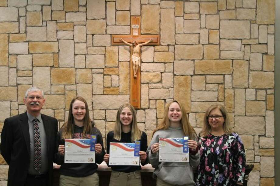 Manistee Catholic Central winners of the 50th Annual America & Me Essay Contest were recently honored by local Farm Bureau Insurance agent Matt Knizacky. Shown left to right are Knizacky, Kaylyn Johnson (first place), Ashley VanAelst (second place), Abigail Logan (third place) and teacher Michelle McComb.