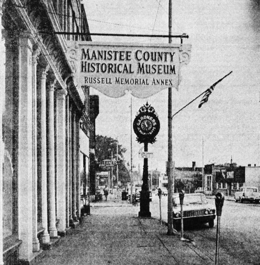This is the 1961 view is of the west end of River Street in front of the Manistee County Historical Museum. The photo also shows how there was two-way traffic on River Street at that time.