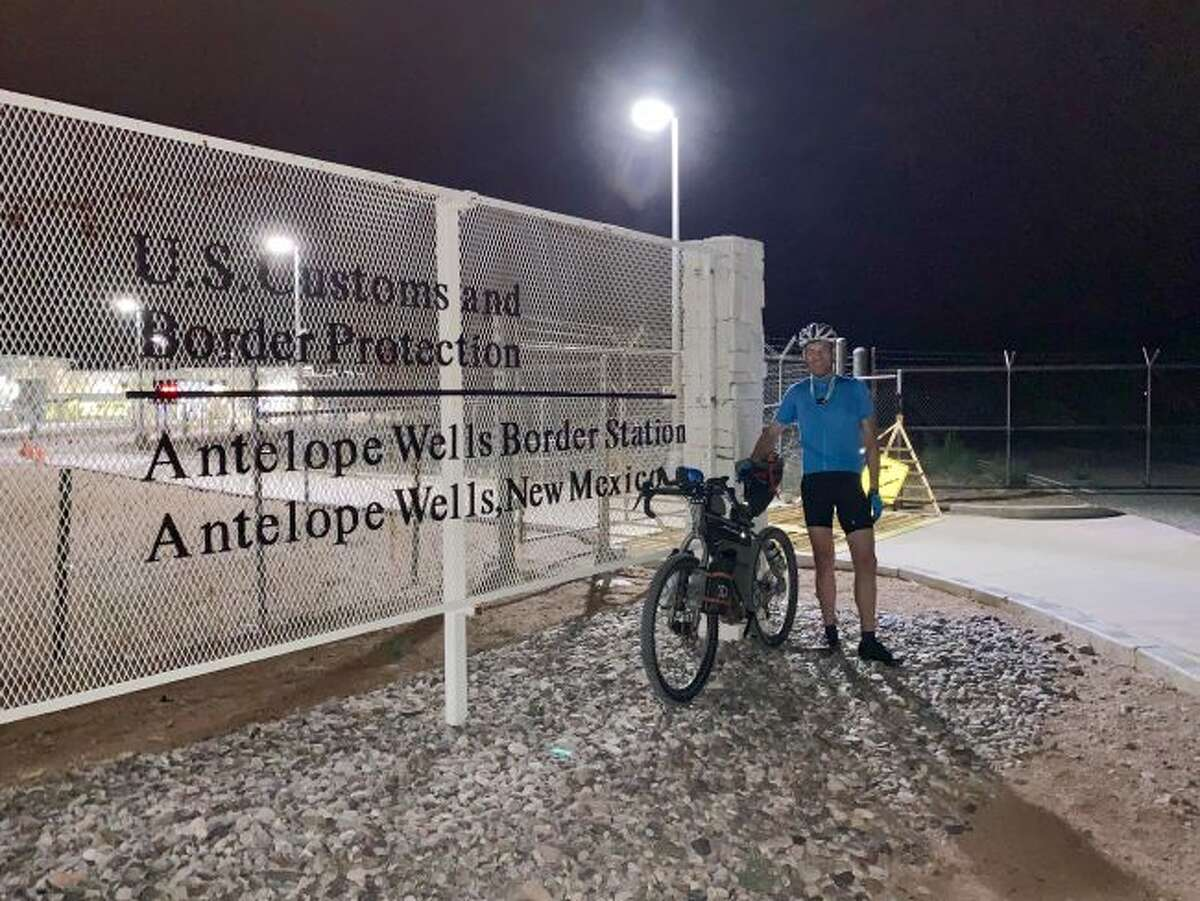Ken Blakey-Shell poses in front of a sign at Antelope Wells, New Mexico where he began his nearly 3,000 mile, 29 day journey this July and August to ride the Great Divide Mountain Bike Route along the Continental Divide to Canada. He started his journey at 3 a.m. in 116 degree heat.