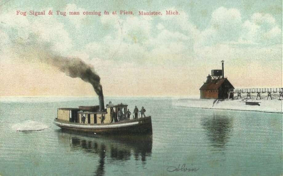 A tug makes its way up the Manistee River channel is this early 1900s photograph