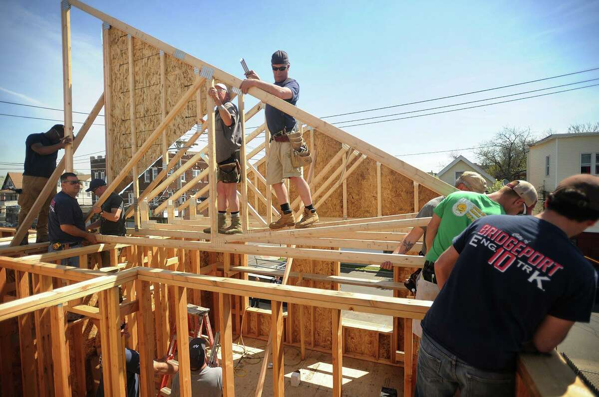 Firefighters from Engine and Ladder 10 in Bridgeport raise the roof trusses on a Habitat for Humanity of Coastal Fairfield County home build last year. The organization will host its 22nd anniversary 5K Run for Home & Workboot Challenge on Oct. 12 at Bridgeport's Seaside Park.
