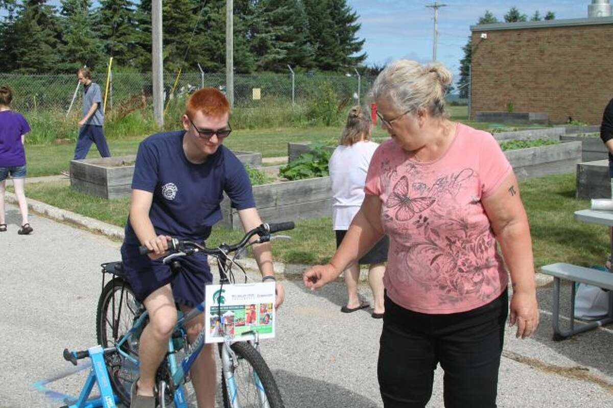 Cyndi Jacobi of the MSU Extension shows a student how to use the Smoothie Bike which allows students to get exercise and to make smoothies at the same time.