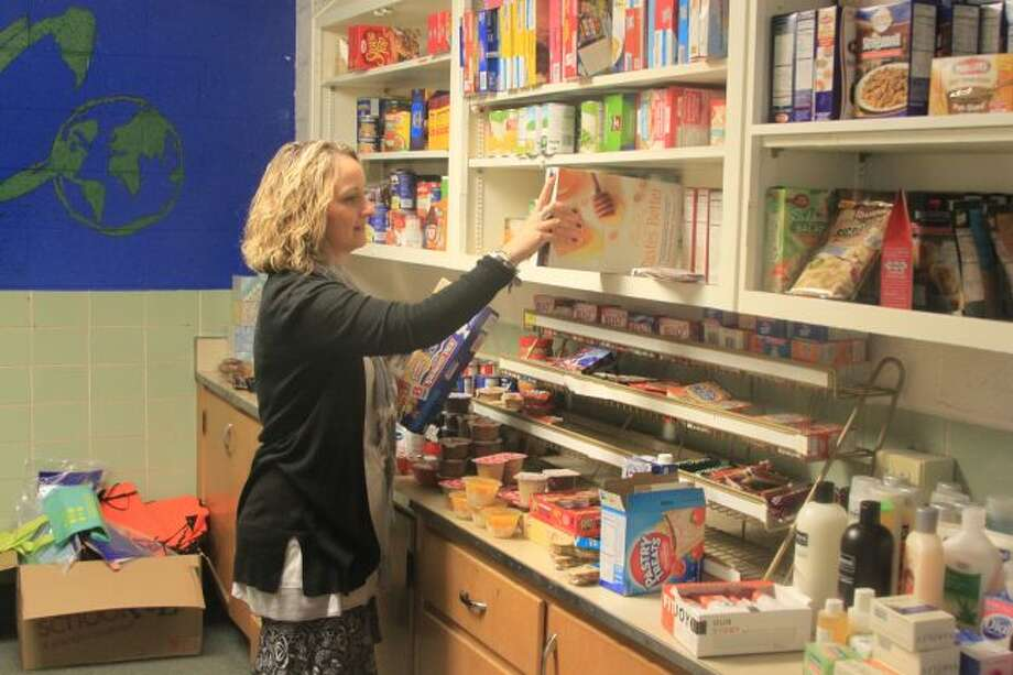 CASMAN Academy director Shelly VanVoorst fills up the food bank at the school that was established assist students for non-perishable food products to give them food to eat at home. The school has a 93 percent free and reduced lunch rate and students are allowed to pick out a back pack full of food for at home when they need it.