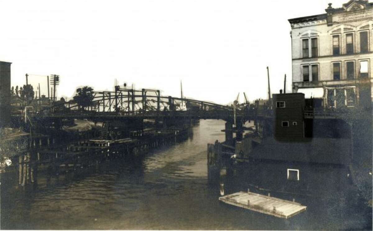 The old version of the Maple Street Bridge from the very early 1900s is shown in this photograph.